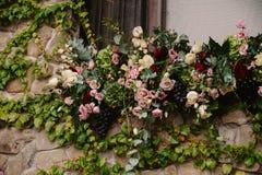 在石墙上的婚姻的花卉构成 图库摄影