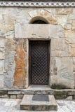 在石墙上的老黑钢门 免版税库存图片