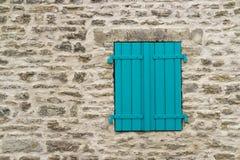 在石墙上的蓝色快门 免版税库存照片