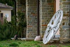 在石墙上的远的西部马车车轮 库存图片