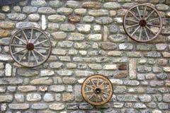 在石墙上的远的西部马车车轮 图库摄影