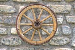 在石墙上的远的西部马车车轮 免版税库存图片