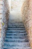 在石墙之间的狭窄的具体步鄹 图库摄影