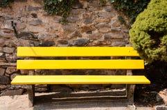 在石墙前面的黄色长凳 免版税库存照片