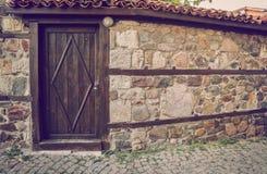 在石墙的老木门 库存照片