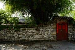 在石墙的遮荫门在瓦片被顶房顶的大厦前 免版税库存图片