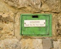 在石墙设置的老绿色捐赠配件箱。 免版税库存图片