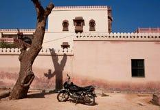 在石墙附近停放的摩托车 免版税库存照片