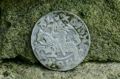 在石墙附近的大老银色中世纪硬币 库存照片