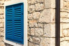 在石大厦的角落的明亮的蓝色葡萄酒窗口快门 库存图片