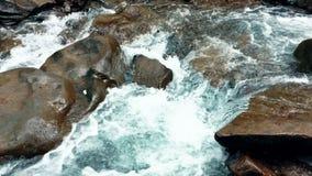 在石头之间的清楚的起泡沫的水小河 E 股票录像
