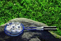 在石头的两副蓝色羽毛球拍 库存照片