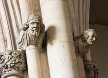 在石头的被雕刻的头在大教堂墙壁上 库存图片
