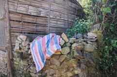 在石头的镶边桃红色,蓝色和白色布料在一个农村地方 免版税库存照片