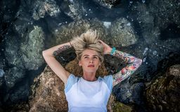 在石头说谎在海附近一个美丽的金发碧眼的女人的画象 妇女有纹身花刺的` s手 现代方式的女孩 免版税库存照片