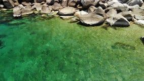 在石头附近的风平浪静水 平安的蓝色海水和灰色冰砾在潜航的完善的地方酸值陶海岛的 股票录像