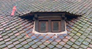 在石屋顶,欧洲的古色古香的木被构筑的窗口 库存图片