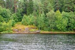在石岸的老被破坏的小船 免版税库存照片
