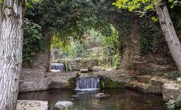 在石曲拱下的小瀑布 免版税图库摄影