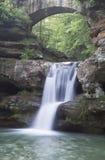 在石曲拱下的瀑布 库存图片