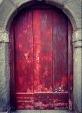 在石曲拱的老红色木门 库存照片