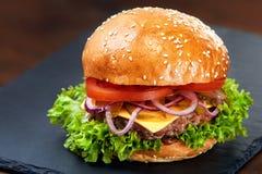 在石桌上的汉堡包有黑背景 快餐膳食 可口汉堡包 美食的汉堡包 免版税库存照片