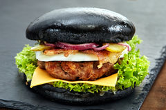 在石桌上的黑汉堡包有黑背景 快餐膳食 可口汉堡包 美食的汉堡包 库存图片