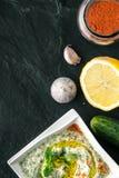 在石桌上的Tzatziki与菜和晒干的垂直 库存图片