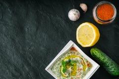 在石桌上的Tzatziki与菜和晒干的顶视图 库存图片