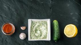 在石桌上的Tzatziki用黄瓜、柠檬和晒干的宽银幕 免版税库存照片
