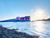在石海岛上的挪威渔村 安静的海湾的走路的红色白色房子 光滑水平面反映 免版税库存图片