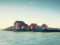 在石海岛上的挪威渔村 安静的海湾的走路的红色白色房子 光滑水平面反映 免版税库存照片