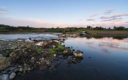 在石海岸和河的日落 库存照片