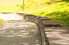 在石海拔的老长木凳在公园 库存图片