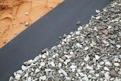 在石渣和含沙地面之间的地布 库存图片