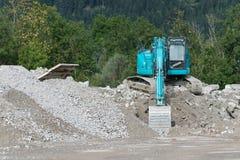 在石渣堆的蓝色铁锹挖掘者 免版税库存图片