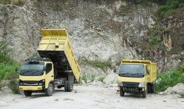 在石灰石猎物的两辆黄色翻斗车 免版税库存照片