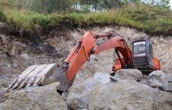 在石灰石猎物的橙色挖掘机 库存照片