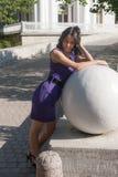 在石球形附近的女孩 免版税库存图片