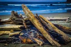 在石矢海滩的营火与海堆在背景中 免版税库存照片