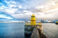 在石码头的灯塔塔在雷克雅未克,冰岛 灯塔在海运 海景和地平线在多云天空 建筑学structur 库存图片