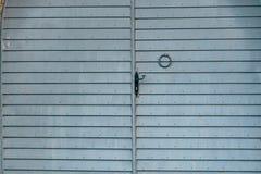在石篱芭的一个青灰色金属门 免版税库存照片
