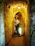在石走廊里面的游人奉承城堡的 图库摄影