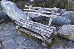 在石头中的老长木凳,家具 库存照片