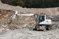 在石头坑的挖掘机 库存照片