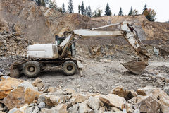 在石头坑的挖掘机 免版税图库摄影