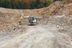 在石头坑的挖掘机 免版税库存照片