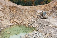 在石头坑的挖掘机 免版税库存图片
