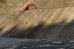 在石头坑的红色挖掘者 库存图片