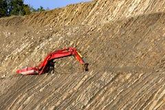 在石头坑的红色挖掘者 库存照片